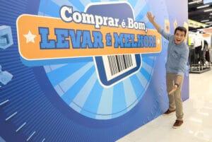 O apresentador Celso Portiolli sorrindo em frente a um painel com o logotipo do game show Comprar é Bom, Levar é Melhor