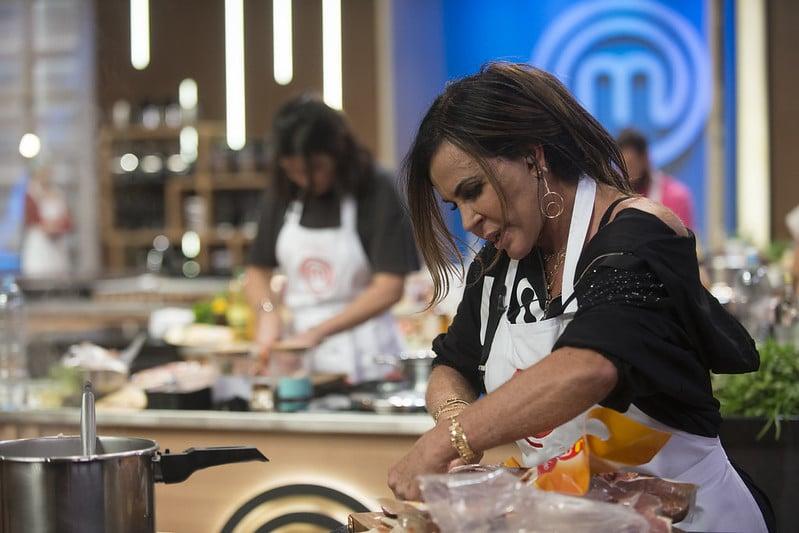 Imagem da cantora Gretchen em uma das bancadas do MasterChef trabalhando na preparação de uma feijoada