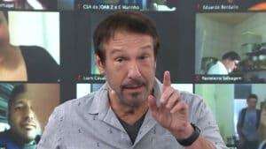 Imagem do apresentador Emílio Surita apontando o dedo para cima no estúdio do programa Pânico