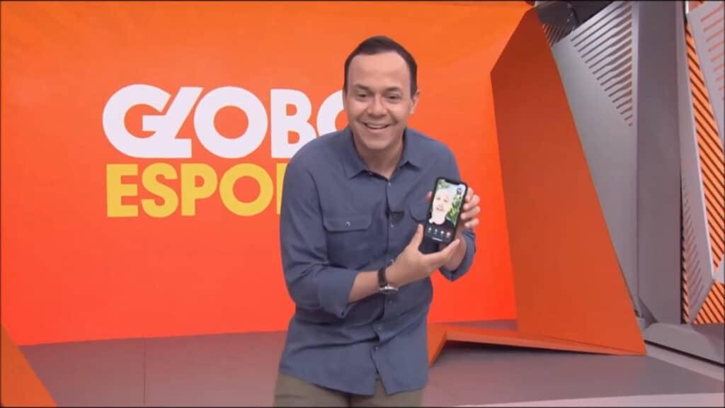 Imagem do apresentador Tiago Medeiros segurando o celular com uma chamada de vídeo para Alex Escobar