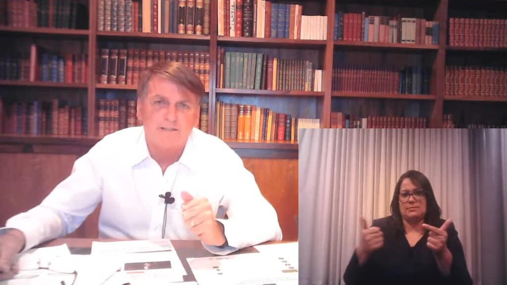 Imagem do presidente Jair Bolsonaro em transmissão nas redes sociais na última quinta-feira (25). Ele aparece com uma biblioteca ao fundo e sentado atrás de uma mesa com papeis. Uma intérprete de libras aparece no canto inferior direito da tela