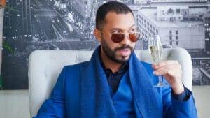 Imagem de Gilberto Nogueira, o Gil do Vigor, segurando uma taça de champanhe em ensaio de fotos