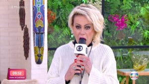Imagem da apresentadora Ana Maria Braga mordendo bolo em formato de microfone