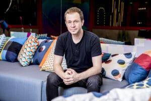 Imagem do apresentador Tiago Leifert sentado no sofá da casa do Big Brother Brasil 21