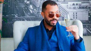 Gil do Vigor posa ao lado de uma taça de champanhe